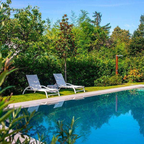 Zoom sur le reflet de la piscine en inox Talya avec transats blancs et douche en bois