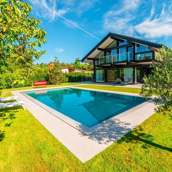 Vue d'ensemble de la piscine en inox Talya avec maison, banc rouge, transats blancs et arbustes