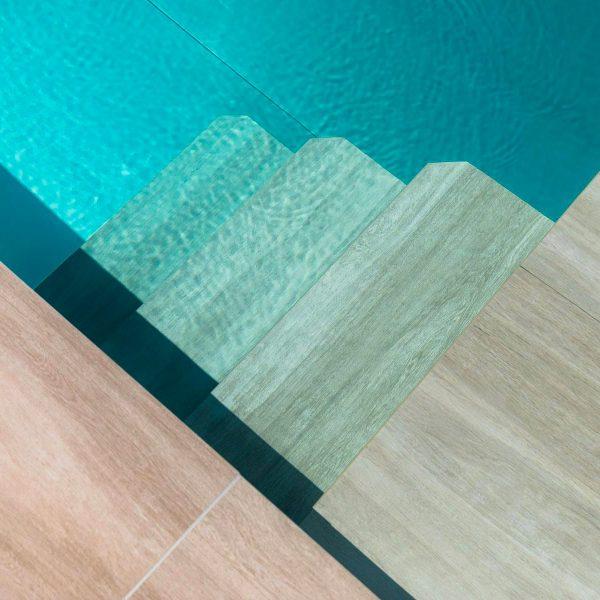 Zoom sur la finition en grès cérame des escaliers de la piscine en inox Talya